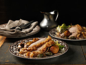 Plated Roast Pork Slices with Crust, Roasted Apples, Caper Berries and Garlic Cloves
