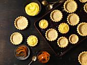 Empty Tarts Shells on Baking Sheet With Bowls of Candied Orange and Lemon Custard