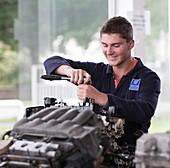 Apprentice mechanic working on an engine