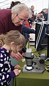 Child looking through a microscope at a science fair