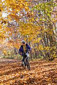 Woman riding a bicycle on a trail, Michigan, USA