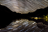 Star trails reflected in mountain lake