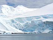 Explorers climbing snow covered slope, Antarctica