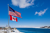 US and Canadian flags at US-Canada border