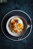 Oats cooked in chicken stock with fried egg, shallots, paprika, chili and parmesan