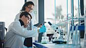 Scientists using pipette in laboratory