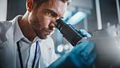 Scientist using a microscope in a laboratory