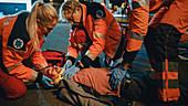 Team of paramedics providing help to an injured man