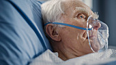 Man wearing oxygen mask in hospital bed