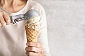 Woman squeezes ice cream scoops on an ice cream cone