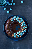 Easter Dark Chocolate Bundt Cake Decorated with Turquois Blue Milk Chocolate Eggs with Marshmallow Center