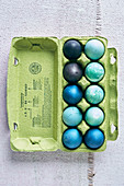 Colorful dyed Easter eggs in shades of blue in an egg carton