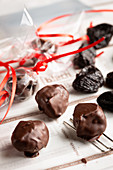 Dried plums with chocolate icing as an edible Christmas decoration
