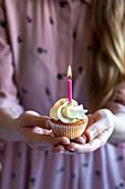 Frau im rosa Kleid und im blonden Haar, die mit zwei Händen einen Cupcake mit einer brennenden rosa Kerze halten