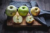 Äpfel, ganz und aufgeschnitten auf Holzbrett