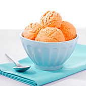 Close-up of 4 scoops of orange colored ice cream in blue bowl