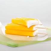 Three orange ice cream popsicles melting