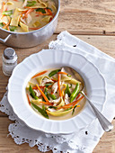 Leckere Frühlingssuppe mit Gemüse, Hühnerfleisch und Bandnudeln