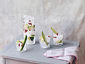 Drei Gläser und eine Karaffe mit Limettensaft, Eiswürfeln, Granatapfelkernen und Gurkengarnitur