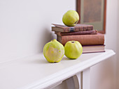 Quince fruit on wooden mantle with old books