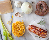 Pasta ingredients - parmesan cheese, white onion, sausage, garlic, rosemary, cured bacon, egg noodles and celery
