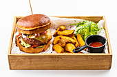American beef burger with potato wedges and tomato sauce
