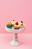 Assorted mini cupcakes on a cake stand against a pink background