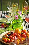 Verschiedene frische Tomaten auf sommerlich gedecktem Gartentisch