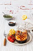 Grilled salmon steak glazed with teriyaki sauce, tomatoes and lemon