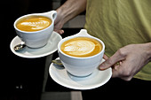 Male barista holding two latte coffees with latte art