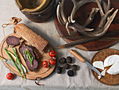 Overhead View of Charcuterie On Wood Boards With Jug, Wooden Bucket, Feathers And Antlers