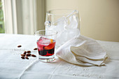 Cocktail With Ice Bucket, Almonds and Cloth Napkin On Table Beside Window