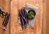 Purple Asapragus and Bowl of Fiddleheads with Scissors On Wood Surface