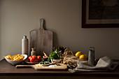 Italienische Zutaten auf Tisch mit Holzschneidebrett in rustikalem Ambiente