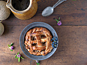 Rustic pie in pewter dish with antique spoon, jug, and melon on wooden surface