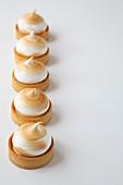 Eine Reihe Zitronen-Baiser-Törtchen auf weißem Hintergrund