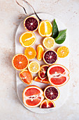 Lemons, grapefruits, oranges and blood oranges cut up on a cutting board