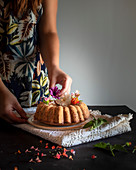 Girl putting some flowers on bundt cake