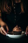 Girl holding a chocolate cupcake