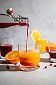 Pomegranate juice being poured into orange juice