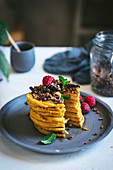 Stacked pumpkin pancakes with granola and raspberries