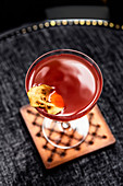 Red cocktail with dried apple slice
