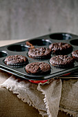 Fresh baked chocolate muffins in baking form