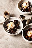 Buchweizen-Brownies serviert in Schälchen mit Eis und Karamellsauce