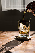 Whiskey being poured into glass with ice cubes