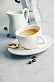 Espresso in white cup with milk and coffee maker