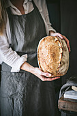 Woman holds homemade sourdough bread in hands