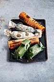 Fisch in Bananenblättern, Woodsheets oder Zeitungspapier gewickelt