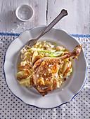 Roasted chicken leg on sauerkraut with apples