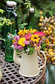 Bunter Sommerblumenstrauß aus Sonnenhut, Zinnie, Schafgarbe, Löwenmäulchen und Witwenblume in Kanne